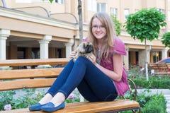 Muchacha con un perro en un banco Imagen de archivo