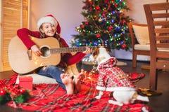 Muchacha con un perro que toca la guitarra y que canta cerca de la Navidad tr Imagenes de archivo