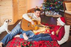 Muchacha con un perro que toca la guitarra y que canta cerca de la Navidad tr Fotos de archivo libres de regalías