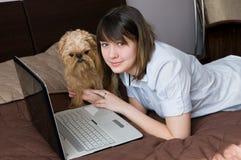 Muchacha con un perro y la computadora portátil Fotos de archivo libres de regalías