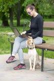 Muchacha con un perro y un ordenador portátil 2017 Fotos de archivo