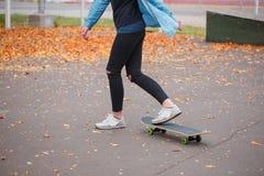 Muchacha con un pie en un monopatín detrás de ella en un parque del patín Fotos de archivo libres de regalías