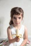 Muchacha con un plátano en su mano Fotos de archivo