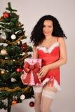 Muchacha con un presente, traje rojo del árbol de navidad y de Santa Claus Imagenes de archivo