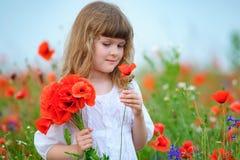 Muchacha con un ramo de amapolas rojas que gozan al aire libre Fotografía de archivo libre de regalías