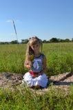 Muchacha con un ramo de flores salvajes en el prado Fotos de archivo libres de regalías