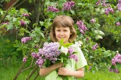 Muchacha con un ramo de lilas Imagen de archivo