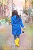Muchacha con un ramo de tulipanes de la primavera en rosa En un impermeable azul y botas amarillas en la calle en Europa Mujer fe foto de archivo