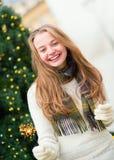 Muchacha con un árbol de navidad cercano de la bengala brillantemente Imagen de archivo