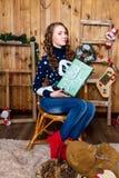 Muchacha con un regalo en su mano que se sienta en el cuarto con wal de madera Imagen de archivo