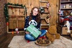 Muchacha con un regalo en su mano que se sienta en el cuarto con wal de madera Fotografía de archivo libre de regalías
