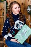 Muchacha con un regalo en su mano que se sienta en el cuarto con wal de madera Imágenes de archivo libres de regalías