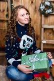 Muchacha con un regalo en su mano que se sienta en el cuarto con wal de madera Imagenes de archivo
