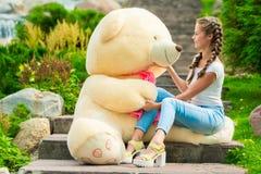 muchacha con un regalo enorme - un oso de peluche en el parque Fotos de archivo