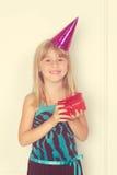 Muchacha con un regalo y un casquillo de cumpleaños Imagen de archivo