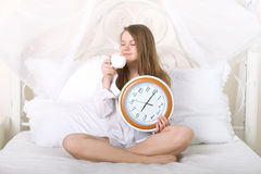 Muchacha con el reloj y la taza en el 5:30  Imagenes de archivo