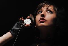 Muchacha con un reloj viejo en una mano Fotos de archivo