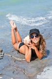 Muchacha con un seashell en el mar. Imagen de archivo