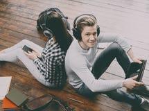 Muchacha con un smartphone y muchacho con una tableta Imagen de archivo