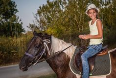 Muchacha con un sombrero que monta un caballo Fotos de archivo