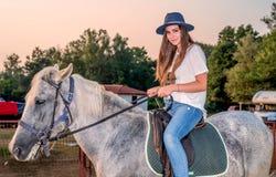 Muchacha con un sombrero que monta un caballo Foto de archivo