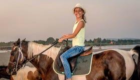 Muchacha con un sombrero que monta un caballo Imagen de archivo libre de regalías