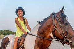 Muchacha con un sombrero que monta un caballo Fotografía de archivo libre de regalías