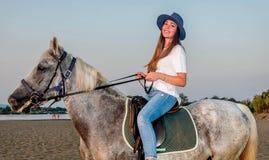 Muchacha con un sombrero que monta un caballo Foto de archivo libre de regalías