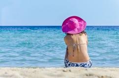 Muchacha con un sombrero rosado en la playa Fotos de archivo