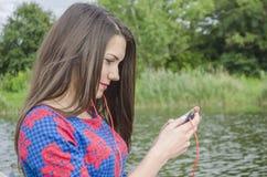 Muchacha con un teléfono afuera Fotos de archivo