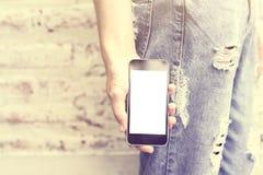 muchacha con un teléfono celular en blanco Fotos de archivo libres de regalías