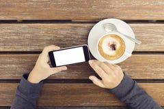 Muchacha con un teléfono celular en blanco y una taza de café en una etiqueta de madera Fotografía de archivo libre de regalías