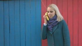 Muchacha con un teléfono del plátano almacen de video