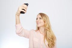 Muchacha con un teléfono elegante Aislado en blanco Fotografía de archivo libre de regalías