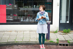 Muchacha con un teléfono elegante que hace una foto Foto de archivo