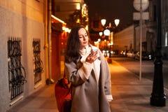 Muchacha con un teléfono en la calle de la ciudad de igualación foto de archivo