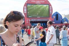 Muchacha con un teléfono en la zona de la fan del mundial 2018 de la FIFA en Samara Fotografía de archivo
