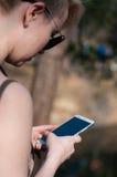 Muchacha con un teléfono en sus manos Fotografía de archivo