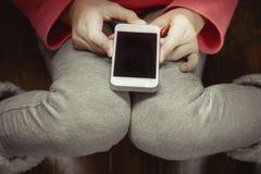 Muchacha con un teléfono en sus manos que se sientan en el piso de madera Visión superior Foto de archivo libre de regalías