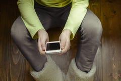 Muchacha con un teléfono en sus manos que se sientan en el piso de madera Visión superior Foto de archivo