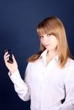 muchacha con un teléfono móvil en una mano, una parte posterior del azul Foto de archivo libre de regalías