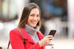 Muchacha con un teléfono que le mira en invierno Foto de archivo