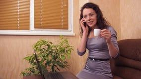 Muchacha con un teléfono y una taza de café Una mujer en un vestido gris dentro detrás de un ordenador portátil con un teléfono e almacen de metraje de vídeo