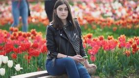 Muchacha con un tel?fono a disposici?n en un campo del tulip?n almacen de metraje de vídeo