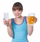 Muchacha con un vidrio de agua y un vidrio de cerveza foto de archivo libre de regalías