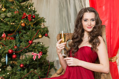 Muchacha con un vidrio de champán en el árbol del Año Nuevo Fotografía de archivo