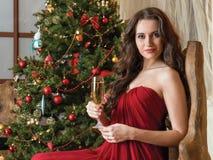 Muchacha con un vidrio de champán en el árbol del Año Nuevo Imagen de archivo