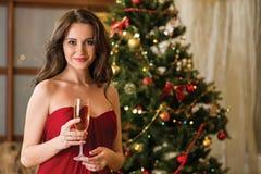 Muchacha con un vidrio de champán en el árbol del Año Nuevo Imagen de archivo libre de regalías