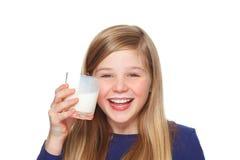 Muchacha con un vidrio de sonrisa de la leche y del bigote de la leche Imagenes de archivo