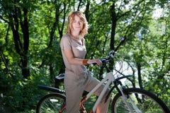 Muchacha con una bicicleta imagen de archivo